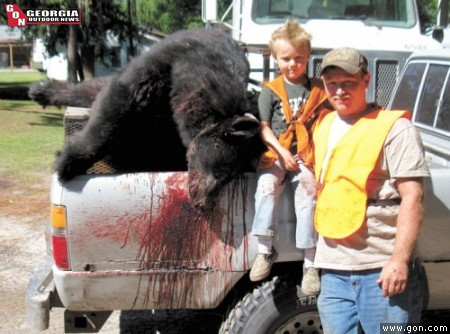 Edward Selph and his son Triston, 6, with the 350-lb. bear Edward wrestled off of Mitch Canaday as the animal mauled the man during a Clinch County hunt Oct. 1.